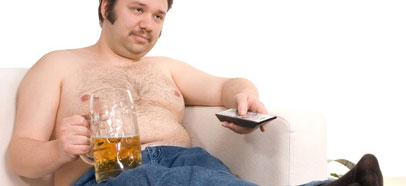 Man that needs to lose weight in a sofa with a beer and a remote control.